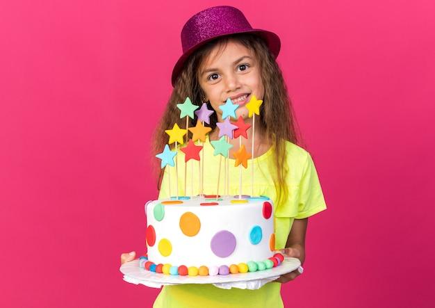 Uśmiechnięta mała kaukaska dziewczynka w fioletowym kapeluszu imprezowym trzymająca tort urodzinowy na różowej ścianie z miejscem na kopię