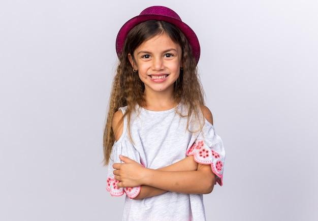 Uśmiechnięta mała kaukaska dziewczynka w fioletowym kapeluszu stojącym ze skrzyżowanymi rękami na białej ścianie z miejscem na kopię