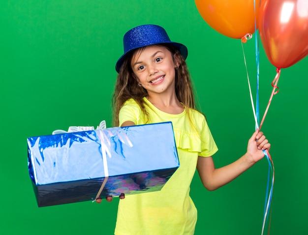Uśmiechnięta mała kaukaska dziewczynka w niebieskim kapeluszu imprezowym trzymająca balony z helem i niebieskie pudełko na prezent na zielonej ścianie z miejscem na kopię