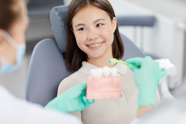 Uśmiechnięta mała kobieta przy dentystami