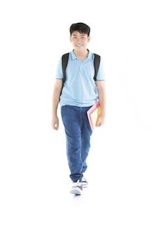 Uśmiechnięta mała studencka chłopiec w błękitnej polo koszulce wewnątrz z książkami i torbą.