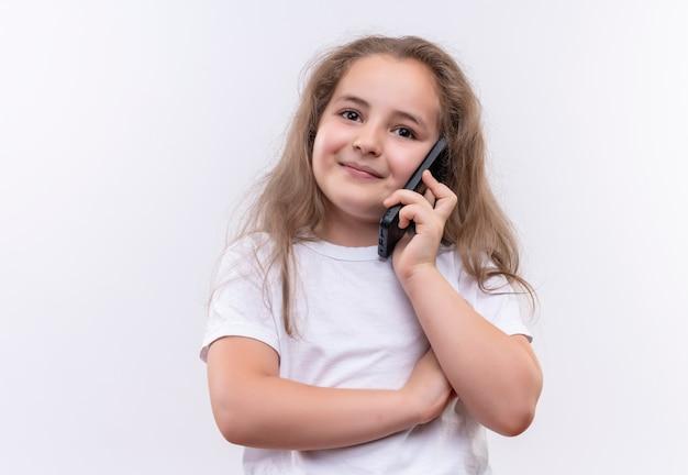 Uśmiechnięta mała uczennica ubrana w białą koszulkę mówi przez telefon na na białym tle