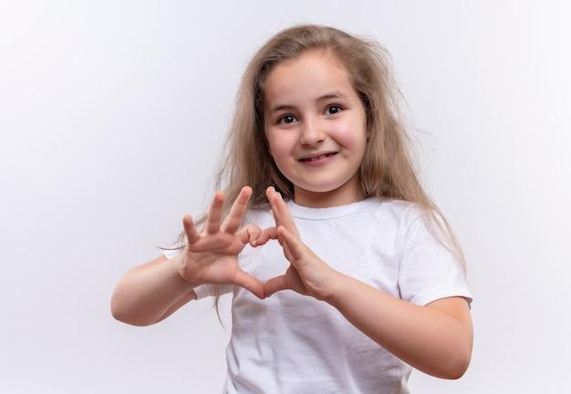 Uśmiechnięta mała uczennica ubrana w białą koszulkę pokazuje gest serca na na białym tle