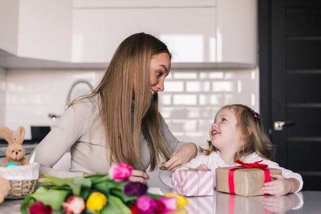 Uśmiechnięta mama daje teraźniejszości jej córka na jej urodziny