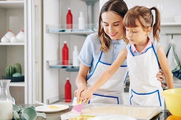 Uśmiechnięta mama pokazująca córce, jak używać silikonowej szpatułki do wygładzania płynnego ciasta na blasze