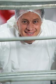 Uśmiechnięta masarki pozycja w mięsnej fabryce