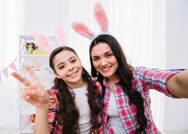 Uśmiechnięta matka i córka jest ubranym królików ucho pokazuje pokoju znaka