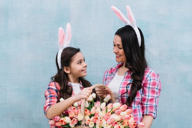 Uśmiechnięta matka i córka jest ubranym królików ucho trzyma tulipany koszykowy patrzejący each inny przeciw błękit ścianie