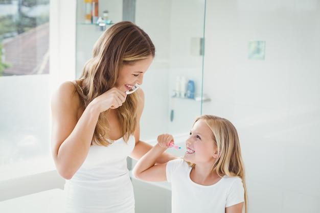 Uśmiechnięta matka i córka myje zęby