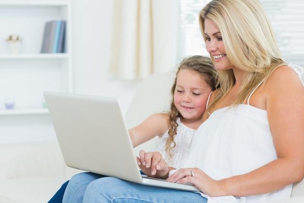 Uśmiechnięta matka i córka na laptopie