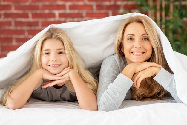 Uśmiechnięta matka i córka patrzeje fotografa
