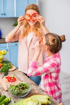 Uśmiechnięta matka i córka patrzeje przez plasterka czerwony dzwonkowy pieprz w kuchni