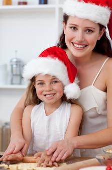 Uśmiechnięta matka i córka piec bożenarodzeniowych torty