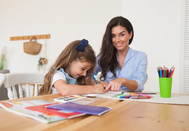 Uśmiechnięta matka i córka przygotowuje się do lekcji i rysuje przy stole ołówkami i farbami