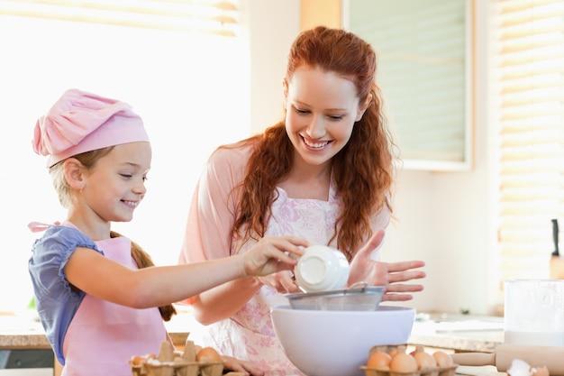 Uśmiechnięta matka i córka przygotowywa ciasto wpólnie