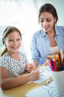 Uśmiechnięta matka i córka rysuje wpólnie