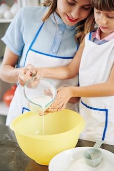 Uśmiechnięta matka i córka wlewając słoik z ciepłym mlekiem do dużej misy z tworzywa sztucznego podczas przygotowywania ciasta naleśnikowego
