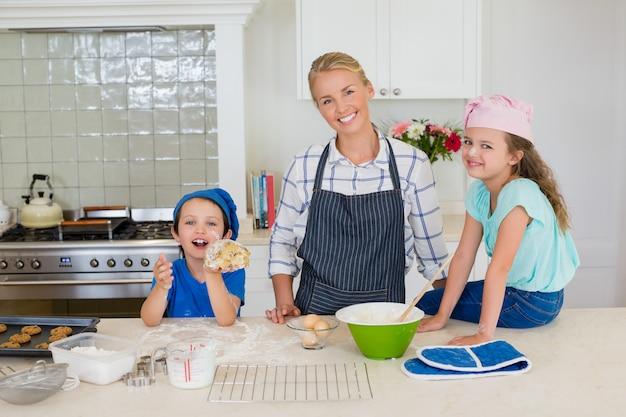 Uśmiechnięta matka i dzieciaki stoi w kuchni