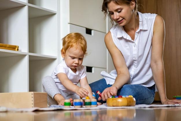 Uśmiechnięta matka i dziecko bawiące się w drewniane zabawki edukacyjne krasnale w beczkach spędzające razem czas