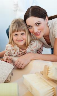 Uśmiechnięta matka i jej córka dekoruje pokój