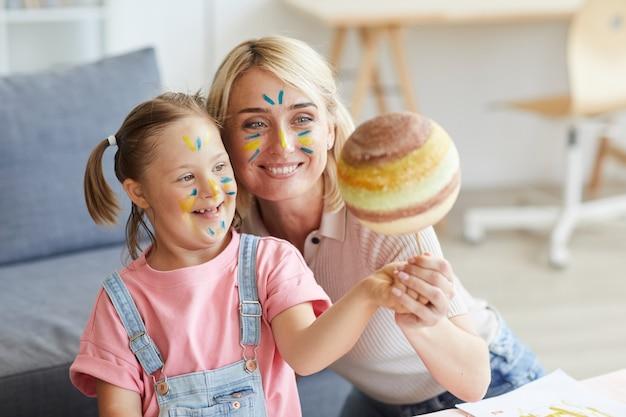 Uśmiechnięta matka pokazująca córce z zespołem downa model planety