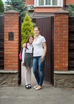 Uśmiechnięta matka przytula córkę idącą do szkoły przed domem