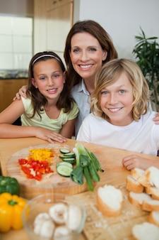 Uśmiechnięta matka robi kanapkom z jej dziećmi