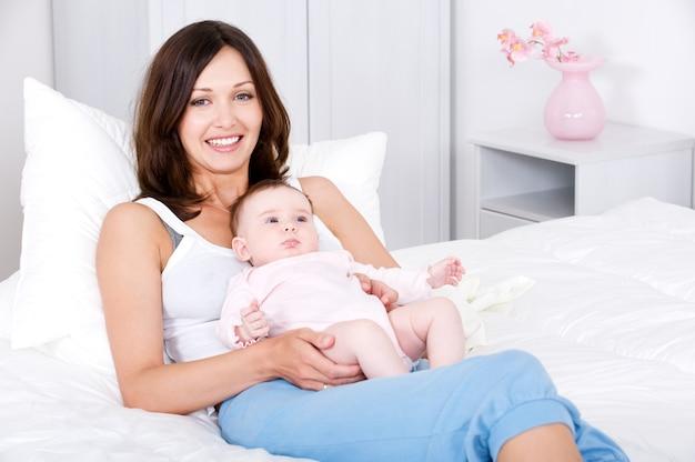 Uśmiechnięta matka siedzi z dzieckiem w domu