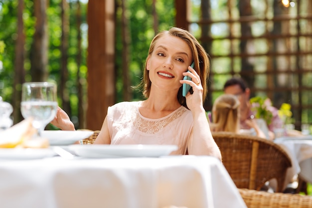 Uśmiechnięta matka. uśmiechnięta, rozpromieniona matka czuje się niesamowicie, dzwoniąc do swojego starszego syna, zapraszającego go na obiad