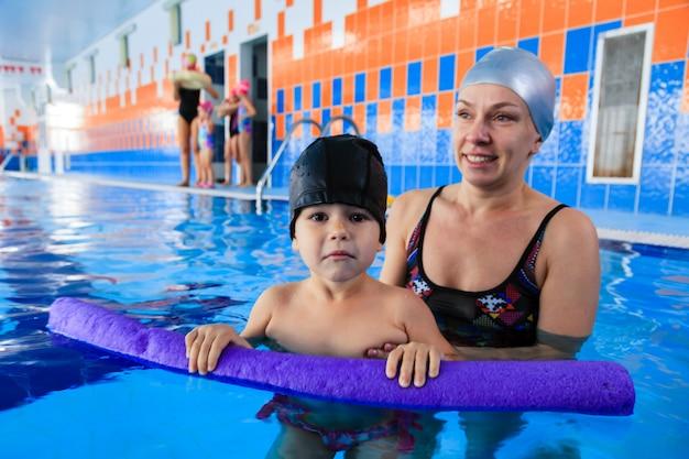 Uśmiechnięta matka w czarnym kostiumie kąpielowym i srebrnej gumowej czapce uczy pływania syna