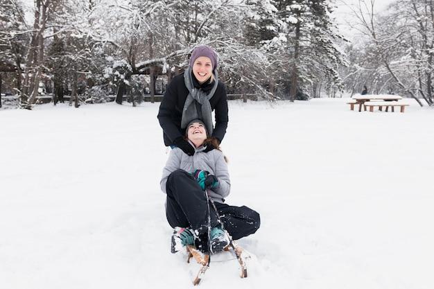 Uśmiechnięta matka z jej córką ma zabawę przy zima dniem