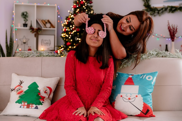 Uśmiechnięta matka zakrywa oczy córki z cukierkiem, siedząc na kanapie, ciesząc się bożonarodzeniowym w domu