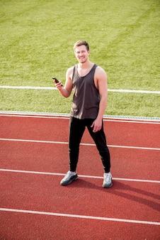 Uśmiechnięta męska atleta stoi na biegowym śladu mienia telefonie komórkowym w ręce