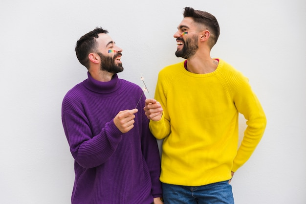 Uśmiechnięta męska para trzyma bengal światła