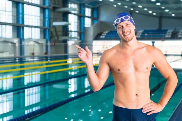Uśmiechnięta męska pływaczka wskazuje jego palec