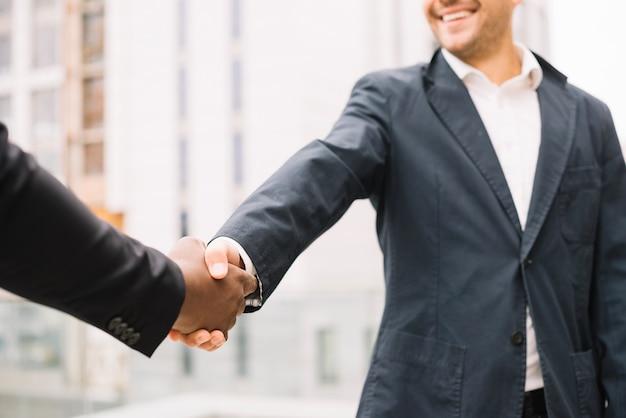 Uśmiechnięta mężczyzna chwiania ręka kolega