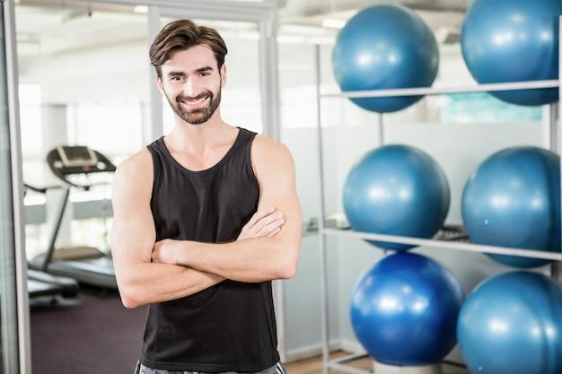Uśmiechnięta mężczyzna pozycja z rękami krzyżował w gym
