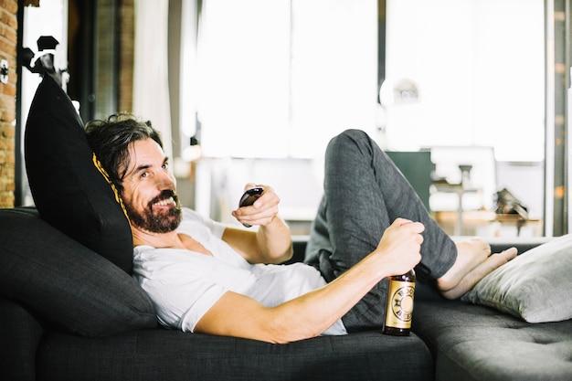 Uśmiechnięta mężczyzna z piwa korzystających z telewizora