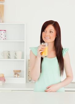 Uśmiechnięta miedzianowłosa kobieta cieszy się szkło sok pomarańczowy w kuchni