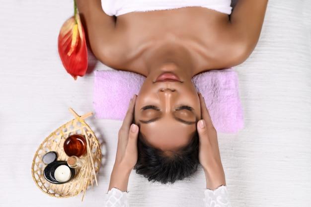 Uśmiechnięta międzyrasowa dziewczyna leży z zamkniętymi oczami na różowym wałku pod głową w ręczniku na stole do masażu i otrzymuje masaż głowy