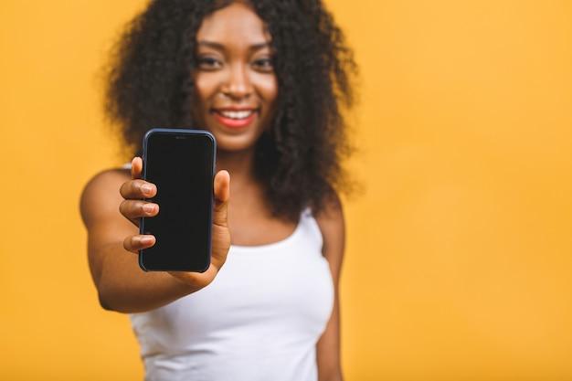 Uśmiechnięta młoda afroamerykanin czarna kobieta trzyma pusty ekran telefonu komórkowego