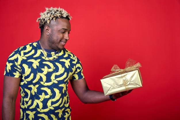 Uśmiechnięta młoda afrykańczyk daje prezent w złotym opakowaniu na czerwonym tle