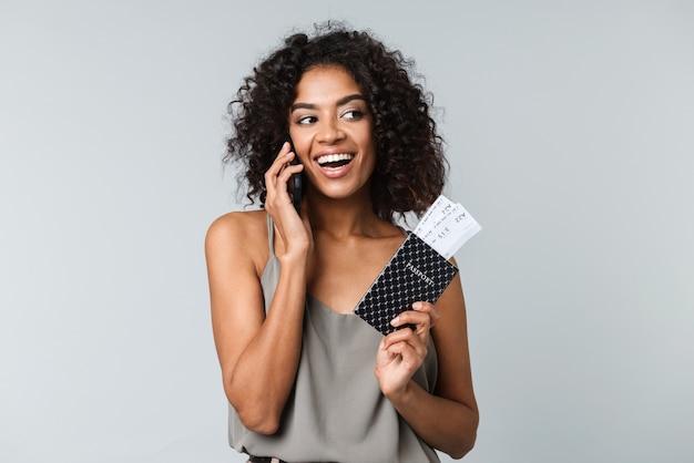 Uśmiechnięta młoda afrykańska kobieta stojąca na białym tle, pokazując bilety lotnicze z paszportem, rozmawiając przez telefon komórkowy