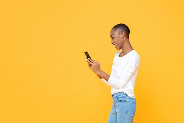 Uśmiechnięta młoda amerykanin afrykańskiego pochodzenia kobieta używa smartphone odizolowywającego na kolor żółty ścianie