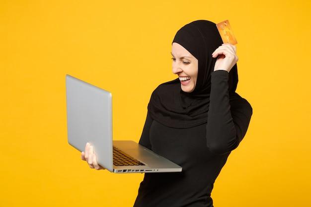 Uśmiechnięta młoda arabska muzułmanka w hidżab czarne ubrania trzymać laptopa, karty kredytowej banku na białym tle na żółty portret ściany. koncepcja życia religijnego ludzi.