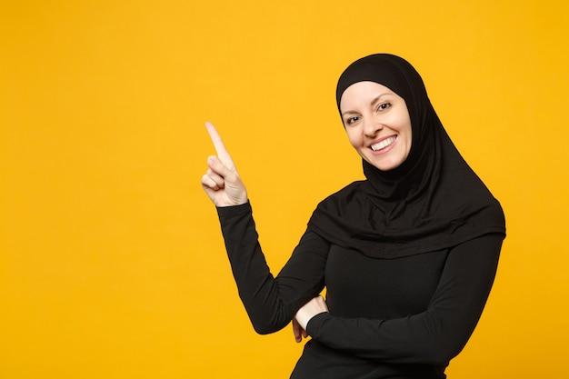 Uśmiechnięta młoda arabska muzułmanka w hidżab czarne ubrania wyświetlono wskazując miejsce z palcem rąk na białym tle na żółtą ścianę portret. koncepcja życia religijnego ludzi.