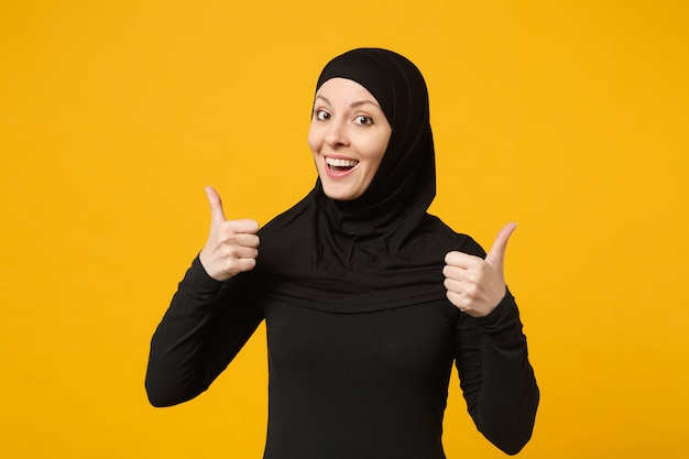 Uśmiechnięta młoda arabska muzułmańska kobieta w hidżab czarne ubrania pokazujące kciuk w górę, na białym tle na żółtej ścianie, portret. koncepcja życia religijnego ludzi.