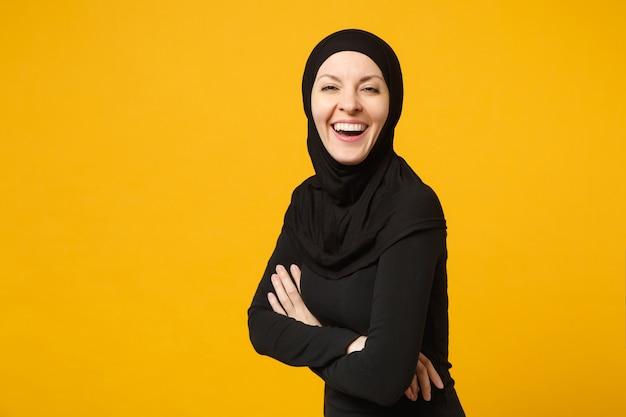 Uśmiechnięta młoda arabska muzułmańska kobieta w hidżab czarne ubrania trzymaj ręce złożone, na białym tle na żółtą ścianę portret. koncepcja życia religijnego ludzi.