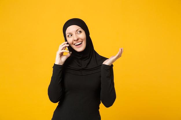 Uśmiechnięta młoda arabskiej kobiety muzułmańskiej w hidżab czarne ubrania trzymać w rękach rozmowy na telefon komórkowy na białym tle portret żółty. koncepcja życia religijnego ludzi. .