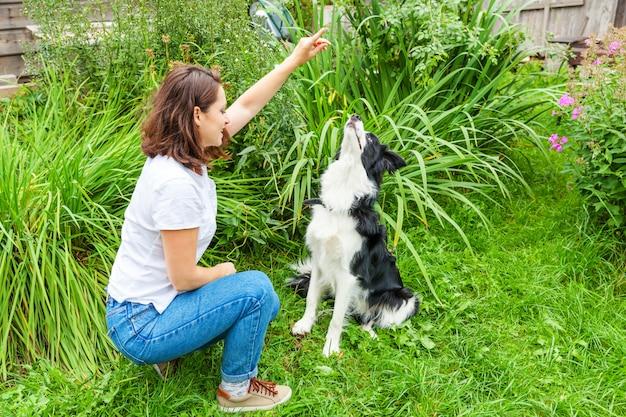 Uśmiechnięta młoda atrakcyjna kobieta bawić się z ślicznym szczeniaka psa border collie w lato ogródzie lub miasto parkowy plenerowym